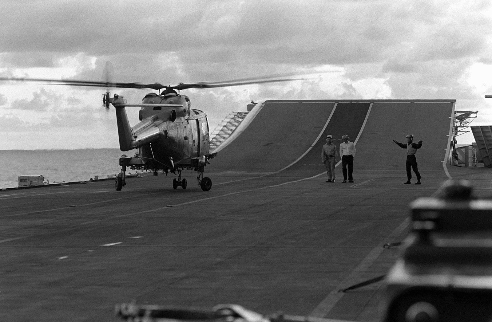 A flight deck crewman signals to the pilot of an HAS  MARK 2