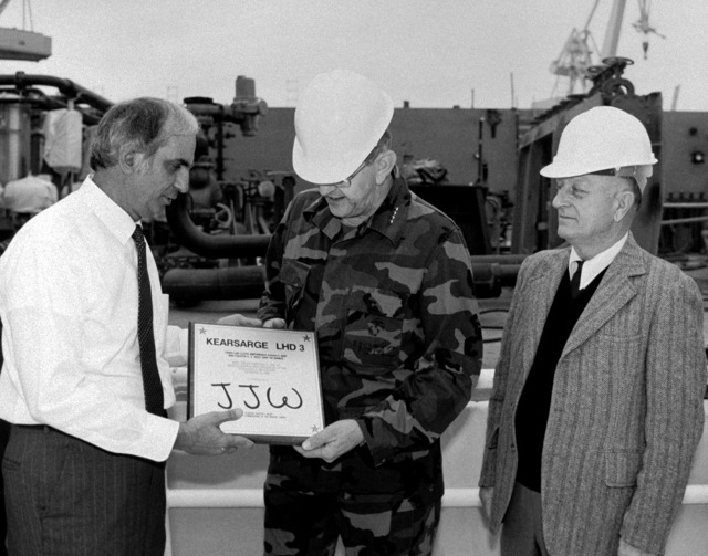 Jerry St. Pe', left, President of Ingalls Shipbuilding, presents a replica of the keel plaque for the amphibious assault ship KEARSARGE (LHD 3) to General (GEN) Joseph J. Went, Assistant Commandant of the Marine Corps, during the keel laying ceremony for the KEARSARGE. At right is E.E. Shouts, program manager, Amphibious Warfare and Strategic Sea Lift Program
