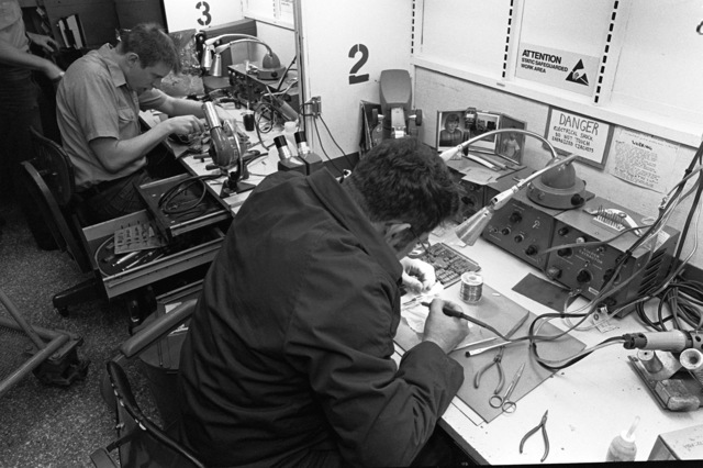 Aviation Fire Control Technician 1ST Class Gregory E. Timmons, foreground, solders an integrated circuit chip onto a circuit board while Aviation Electrician's Mate 3rd Class James G. Frahm splices wires in an Aircraft Intermediate Maintenance Department (AIMD) repair shop aboard the aircraft carrier USS JOHN F. KENNEDY (CV-67) during Fleet Ex 1-90