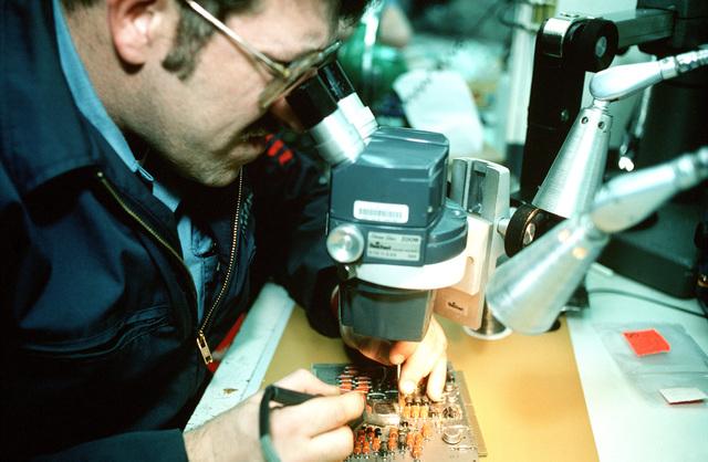 Aviation Fire Control Technician 1ST Class Gregory E. Timmons solders an integrated circuit chip onto a circuit board in an Aircraft Intermediate Maintenance Department (AIMD) repair shop aboard the aircraft carrier USS JOHN F. KENNEDY (CV-67) during Fleet Ex 1-90