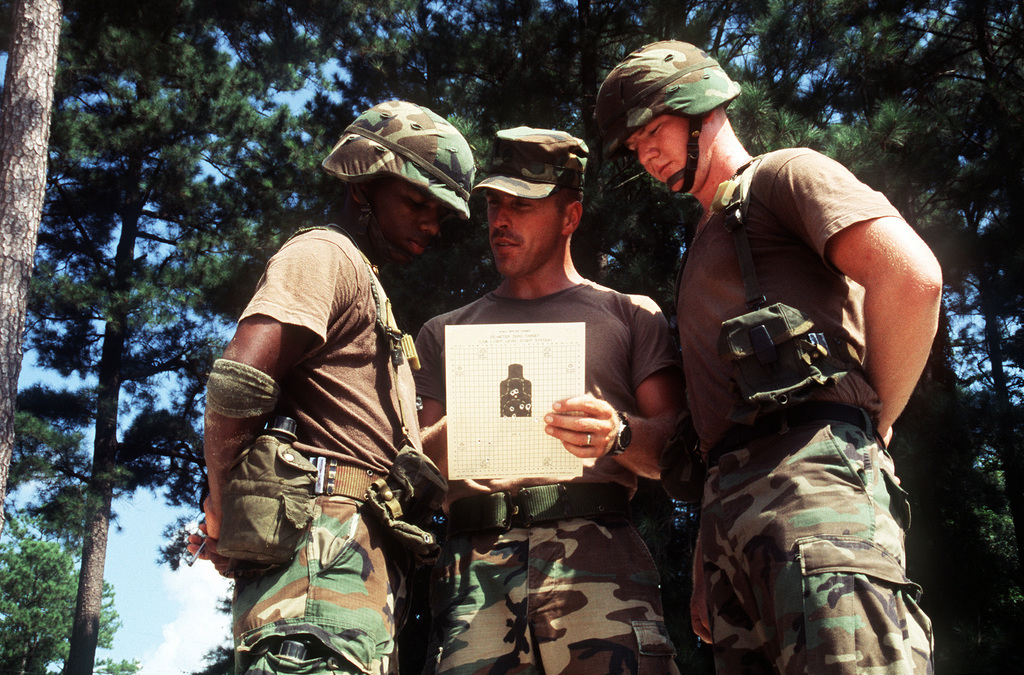 An Instructor And Two Recruits Review A Rifle Qualification Score