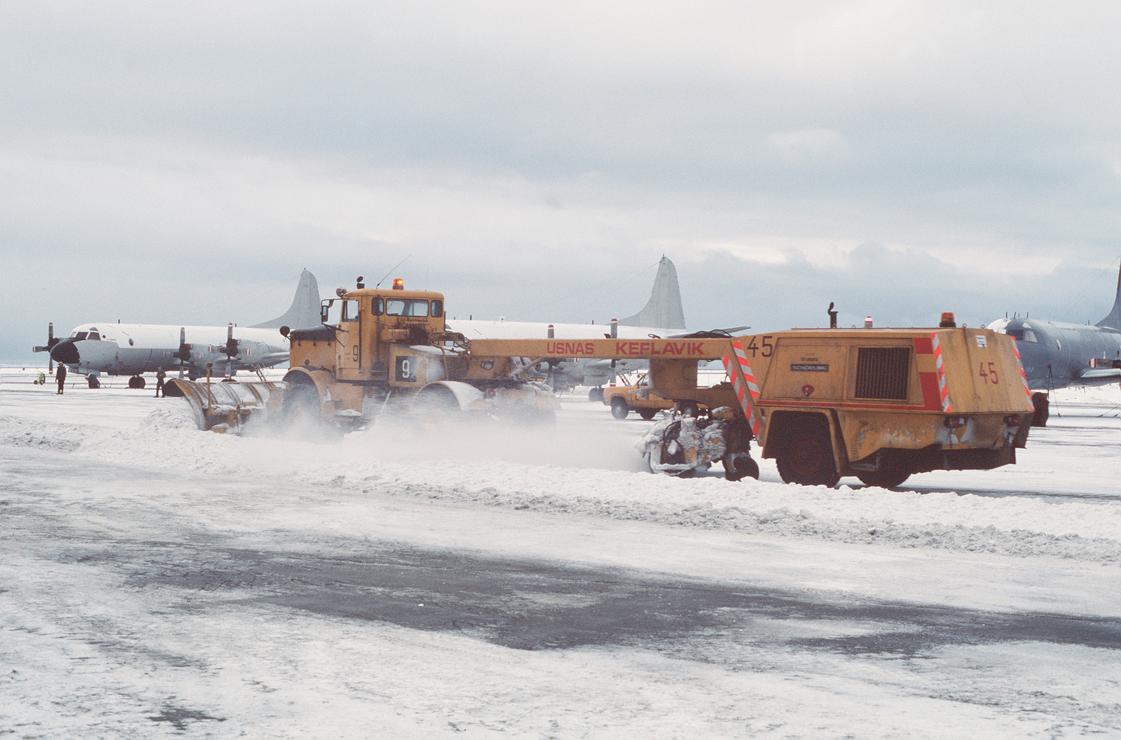 Heavy equipment removes snow from the flight line in front of a row of P-3 Orion aircraft