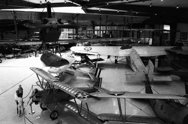 A view of some of the aircraft on display at the US Naval Aviation Museum. On the floor, clockwise from lower right, are an FF-1 fighter aircraft, an NT-1 trainer aircraft, an F-6C-1 Hawk aircraft, an S-4C advanced trainer aircraft and an RR-5 transport aircraft. Hanging from the ceiling at upper left is a Curtiss N-9 seaplane