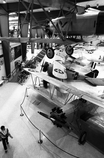 A view of some of the aircraft on display at the US Naval Aviation Museum. On the floor, clockwise from lower right, are an N2C-2 Fledgling trainer aircraft, an FF-1 fighter aircraft, an NT-1 trainer aircraft. A TS-1 fighter aircraft hangs from the ceiling at upper right