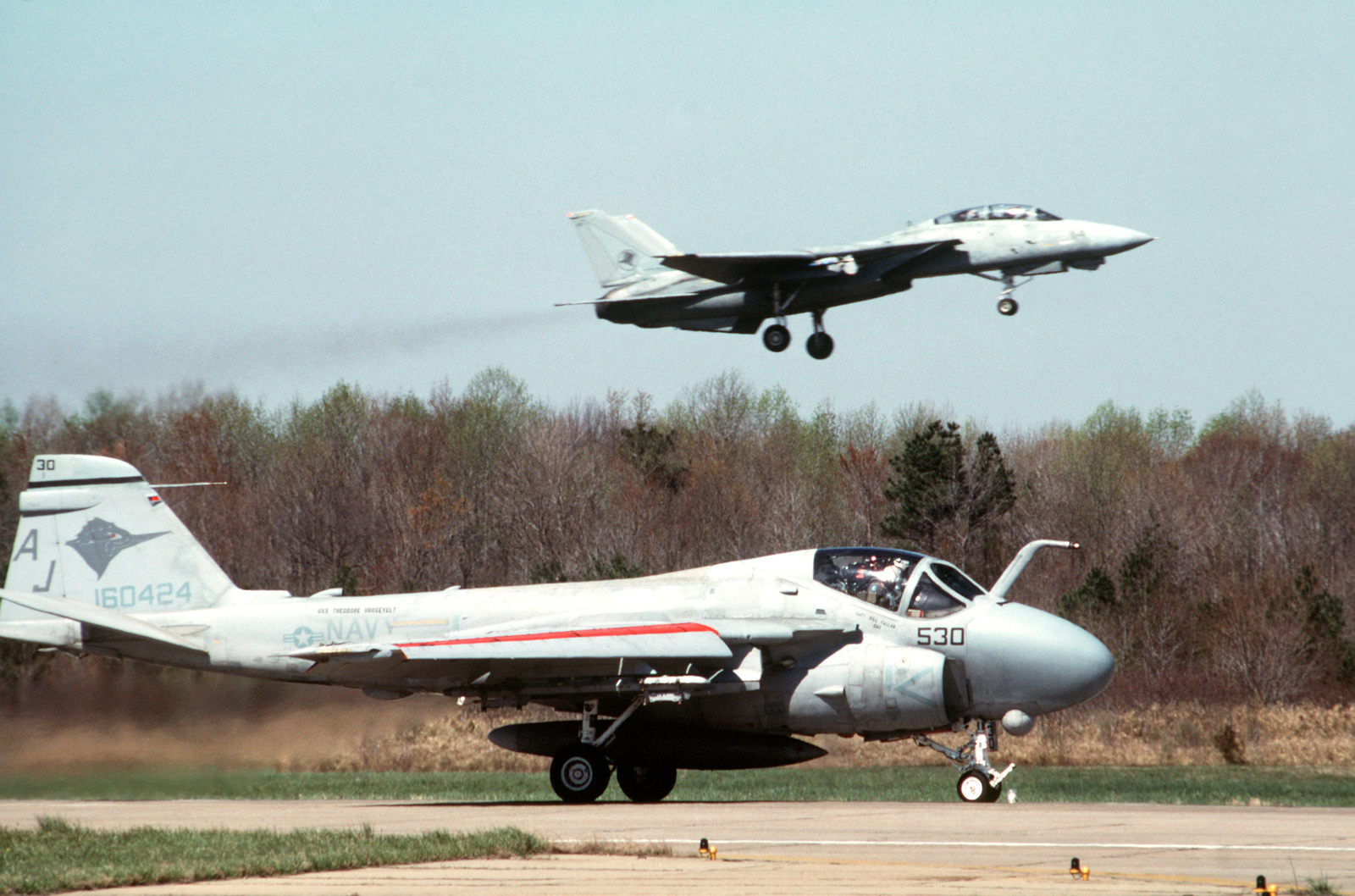 An Attack Squadron 36 (VA-36) A-6E Intruder aircraft rolls along a runway as a Fighter Squadron 14 (VF-14) F-14A Tomcat aircraft passes overhead