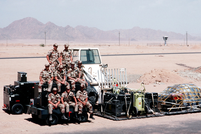 Airmen from the 435th Tactical Airlift Wing's airlift control element (ALCE) and the 4th Mobile Aerial Port Squadron gather for a group photograph at the Ras Nusrani airfield. The airmen are in Egypt to coordinate aircraft operations connected with the arrival and departure of United States forces serving with the Multinational Force and Observers (MFO) peacekeepers on the Sinai Peninsula