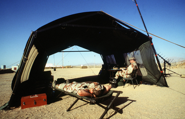 SSGT Dave Rauer relaxes as TSGT John Paulus monitors the radio near the Ras Nusrani airfield. The two airmen, both members of the 435th Tactical Airlift Wing's airlift control element (ALCE) are part of a nine-man detachment sent to Egypt to coordinate aircraft operations connected with the arrival and departure of United States forces serving with the Multinational Force and Observers (MFO) peacekeepers on the Sinai Peninsula