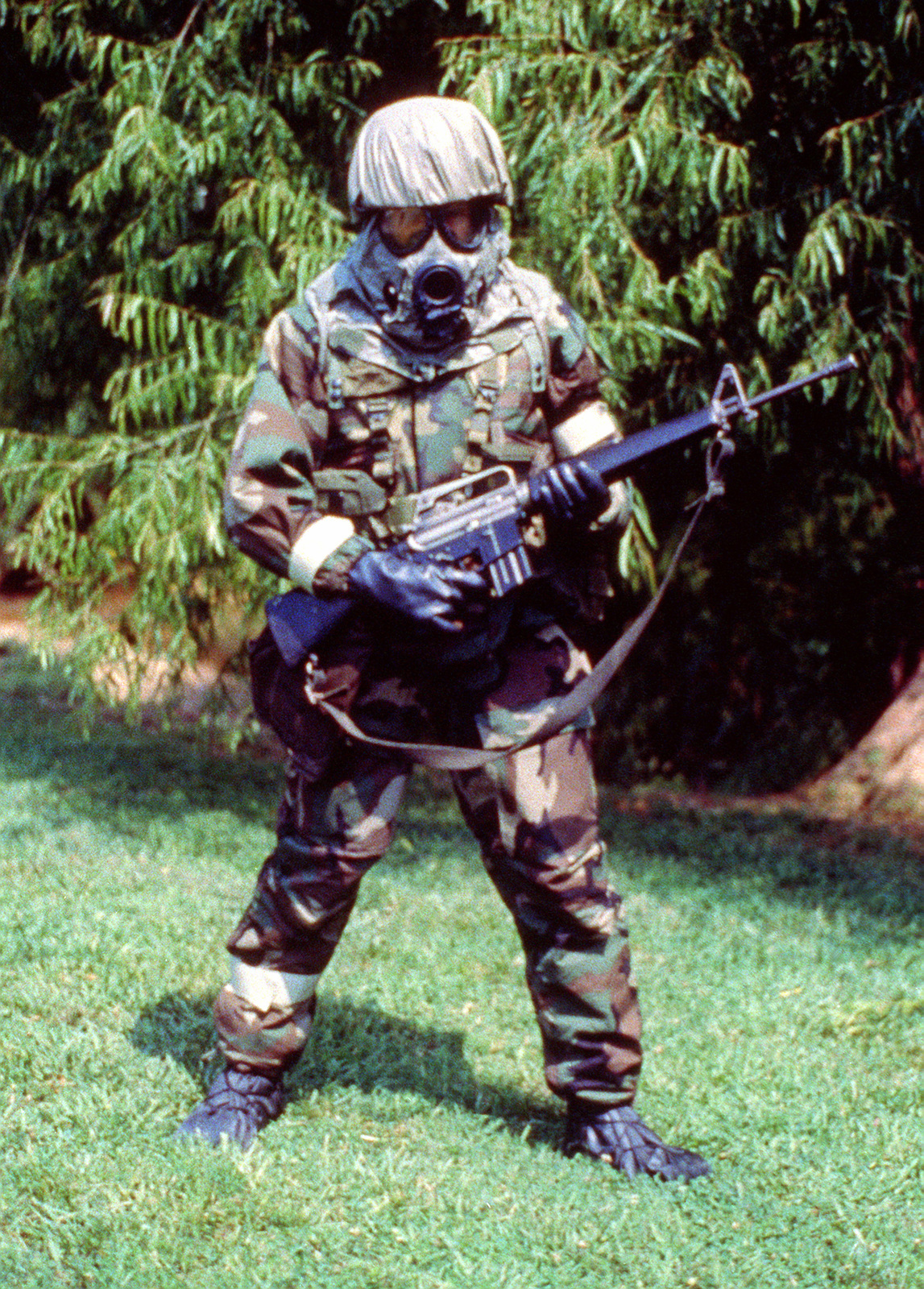 A soldier wearing Mission-Oriented Protective Posture response level 4 (MOPP-4) gear, including an M-17A1 mask, and a M-16A1 rifle