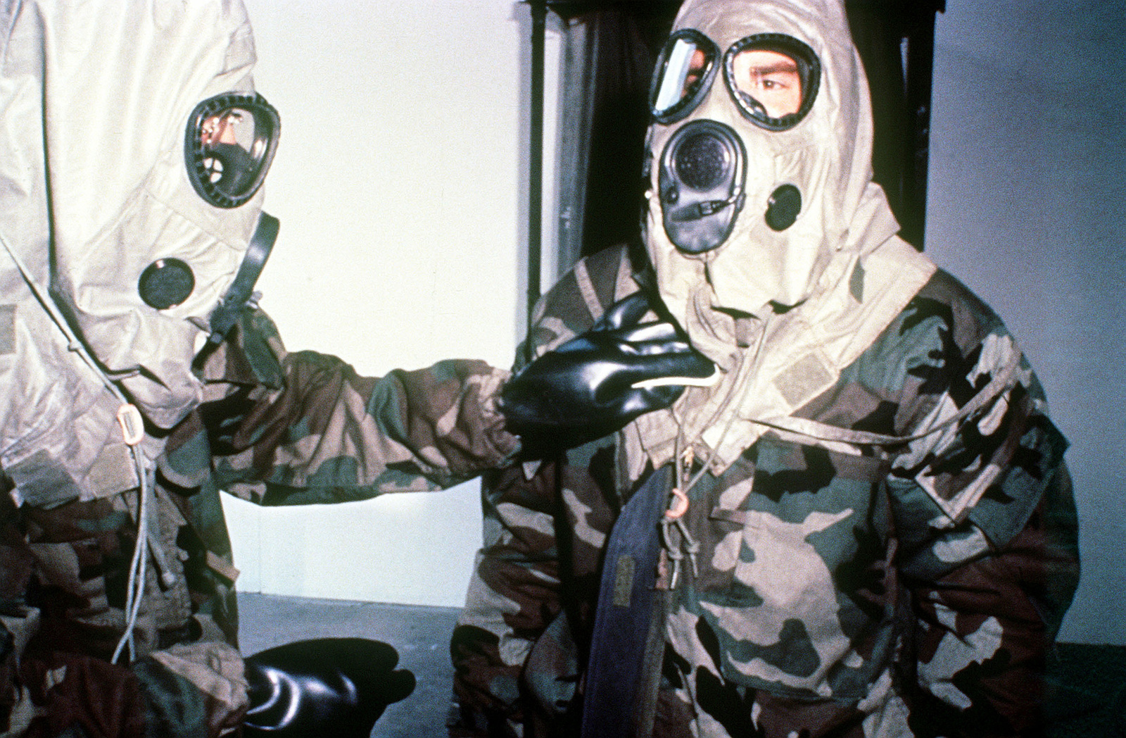 Two soldiers demonstrate mission-oriented protective posture (MOPP) Level IV gear, including M-17A1 masks