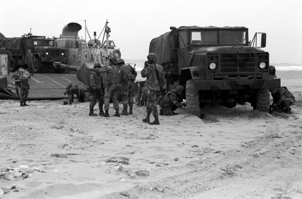 To gain additional traction in the soft sand, Marines lower the air pressure in the tires on their M-923 5-ton cargo truck and on the carriage of the M-198 155mm howitzer it is towing. The Marines have just driven ashore off of the air cushion landing craft LCAC-18 on D-day of the combined South Korean/U.S. exercise Team Spirit '90