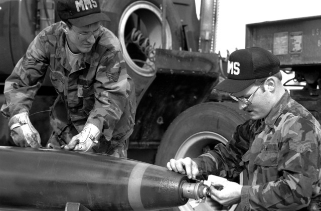 AIC Sam Greendorfer and SRA Doug Klugman, 92nd Munitions Maintenance Squadron, attach an arming wire to the nose fuse of a Mark 82 500-lb bomb