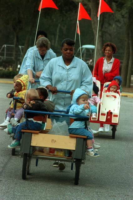 Cartloads of toddlers enjoy an outing with Naval Air Station Child Development Center staffers, from far left: Jackie Kennedy, Sarah Parks, Martha Parker and Ida Maxwell. Center staff members try to create an atmosphere conducive to learning as well as fun for the children of Navy personnel