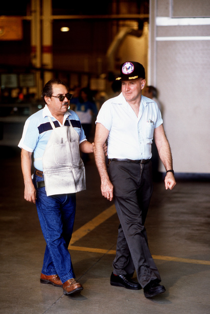 Tomas Vilareal, left, and Gene Moore make their way across the floor at the base's San Antonio Air Logistics Center. Villareal and Moore are among the five visually impaired men who work in the center as turbine blade inspectors. The heightened sensitivity in the fingers of these men allows them to detect flaws not visible to the naked eye