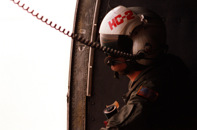 A member of Helicopter Combat Support Squadron 2 (HC-2) looks out the open door of an SH-3 Sea King helicopter as it flies out to the nuclear-powered aircraft carrier USS THEODORE ROOSEVELT (CVN-71) in the aftermath of Operation Desert Storm