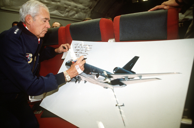 "GEN John T. Chain Jr., commander-in-chief, Strategic Air Command, autographs prints of a KC-10A Extender aircraft as the plane, ""The Spirit of Kitty Hawk"", is en route to Seymour Johnson Air Force Base, home of the 68th Aerial Refueling Wing (68th AREFW), following a transfer ceremony at McDonnell Douglas' Long Beach plant. The plane is the twentieth and final KC-10A to be received by the 68th AREFW and the final KC-10A to be delivered to the Air Force"