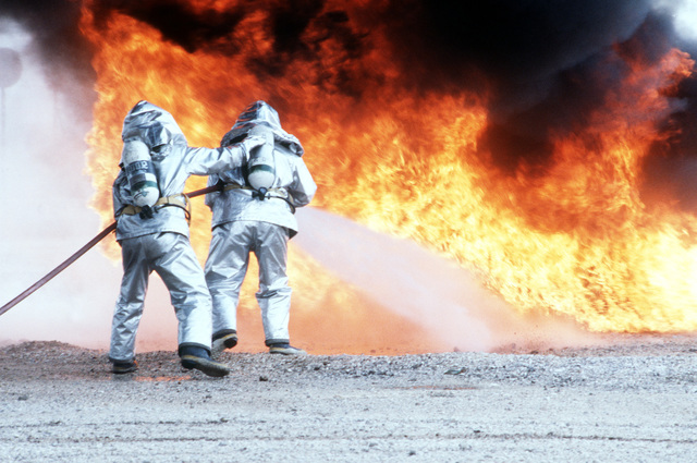 Dressed in proximity suits two firefighters battle a practice fire during a Salty Nation exercise. The 401st Tactical Fighter Wing has deployed to Aviano from Torrejon Air Base, Spain, for the exercise