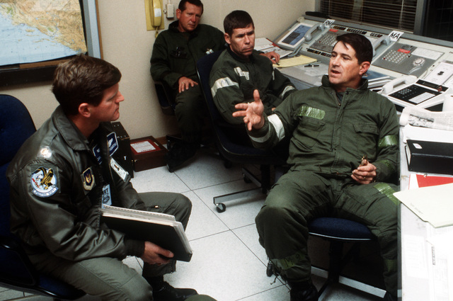 MAJ Carl D. Rebarchak, left, an exercise evaluator, talks with officers from the 401st Tactical Fighter Wing (401st TFW) during a Salty National exercise. The 401st TFW has deployed to Aviano from Torrejon Air Base, Spain, for the exercise