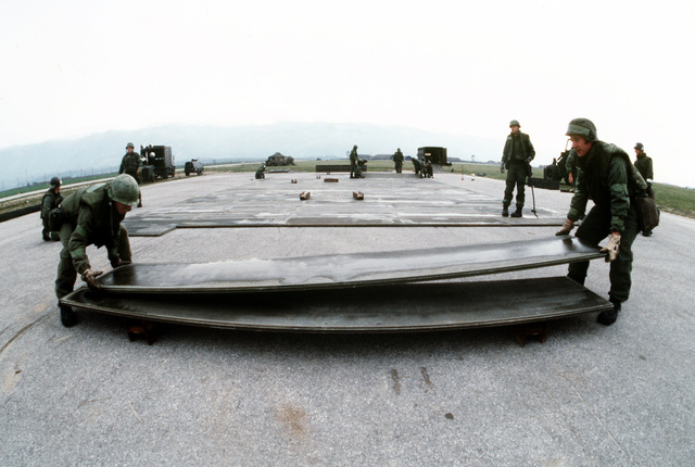 Members of a rapid runway repair team assemble sections of aluminum matting during a Salty Nation exercise. The 401st Tactical Fighter Wing has deployed to Aviano from Torrejon Air Base, Spain, for the exercise