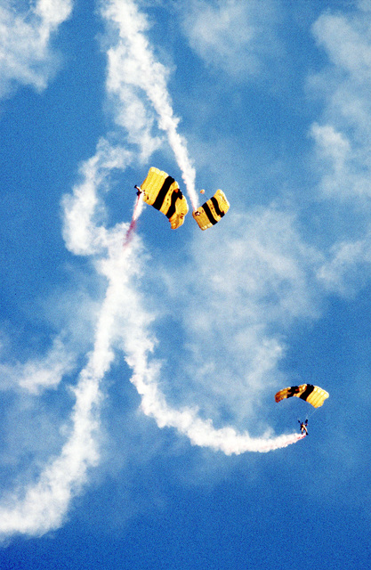 Trailing plumes of smoke, three members of the U.S. Army's Golden Knights parachute demonstration team maneuver around one another during a practice jump into Laurinburg Drop Zone