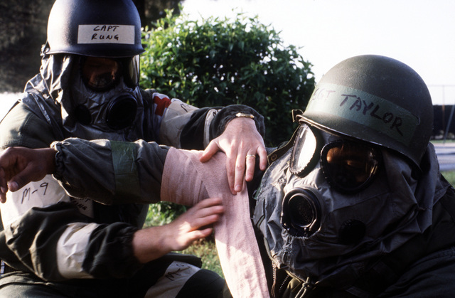 Wearing protective clothing and an M-17A1 field protective mask, a doctor treats a simulated casualty as a nuclear-biological-chemical (NBC) drill is conducted during a Salty Nation exercise. The 401st Tactical Fighter Wing has deployed to Aviano from Torrejon Air Base, Spain, for the exercise