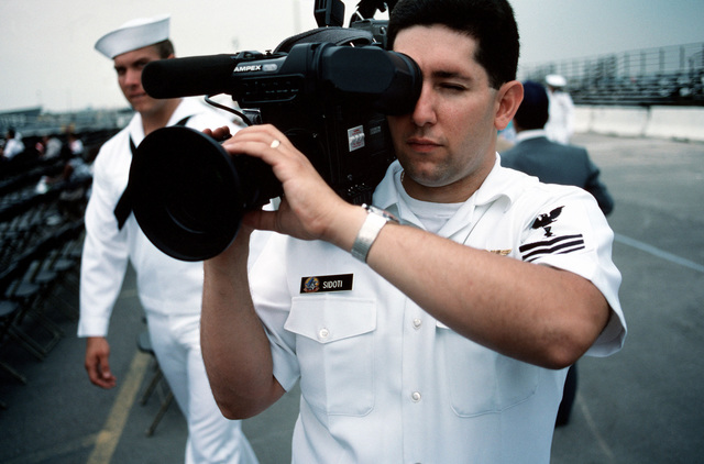 A photographer's mate videotapes proceedings at the commissioning of the guided missile cruiser MONTEREY (CG 61)