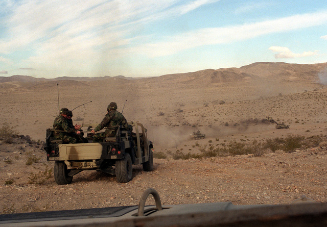 STAFF officers watch from the back of an M998 High-Mobility Multipurpose Wheeled Vehicle (HMMWV) as a column of Opposing Forces (OpFor) armored vehicles advances toward an engagement with the Blue Forces during an exercise