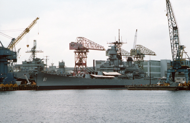 The battleship USS IOWA (BB 61) lies tied up for post-deployment maintenance at the Norfolk Naval Shipyard. The IOWS's SPS-49 air search radar and other antennas have been removed in anticipation of the ship's deactivation, which is scheduled for October 1990