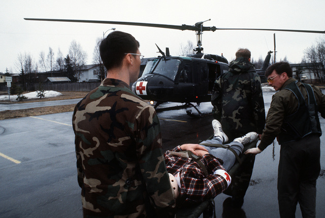 Medical personnel of the Alaska Army National Guard carry an earthquake victim to a UH-1 Iroquois helicopter during a medical evacuation exercise