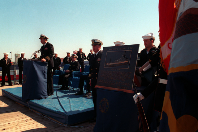 CAPT. Fred P. Moosally, commanding officer of the battleship USS IOWA (BB-61), speaks at a shipboard ceremony marking the one-year anniversary of the gun turret explosion that killed 47 sailors aboard the ship. A plaque bearing the names of the men who died is being dedicated during the ceremony