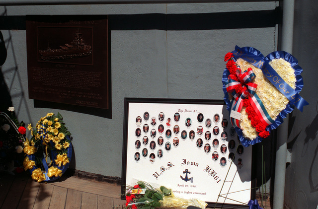 Following the dedication of a plaque bearing the names of the 47 sailors killed in April 19, 1989, gun turret explosion aboard the battleship USS IOWA (BB-61), flowers and other mementos lean against a bulkhead near the plaque