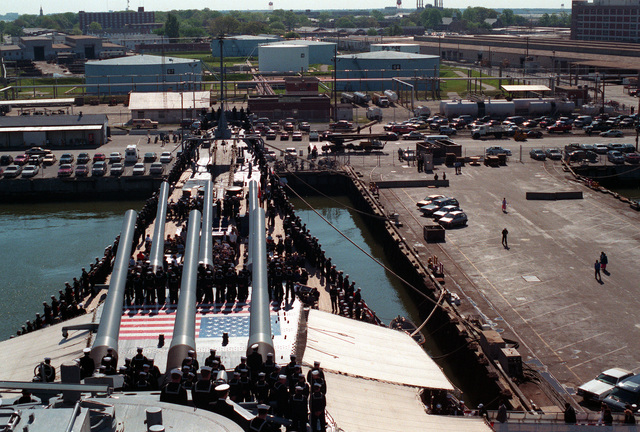 The crew of the battleship USS IOWA (BB-61) and the families of the 47 sailors killed aboard the ship in the April 19, 1989, gun turret explosion aboard the battleship USS IOWA (BB-61) attend a shipboard ceremony with the IOWA's crew on the one-year anniversary of the explosion. A plaque bearing the names of the men who died is being dedicated during the ceremony