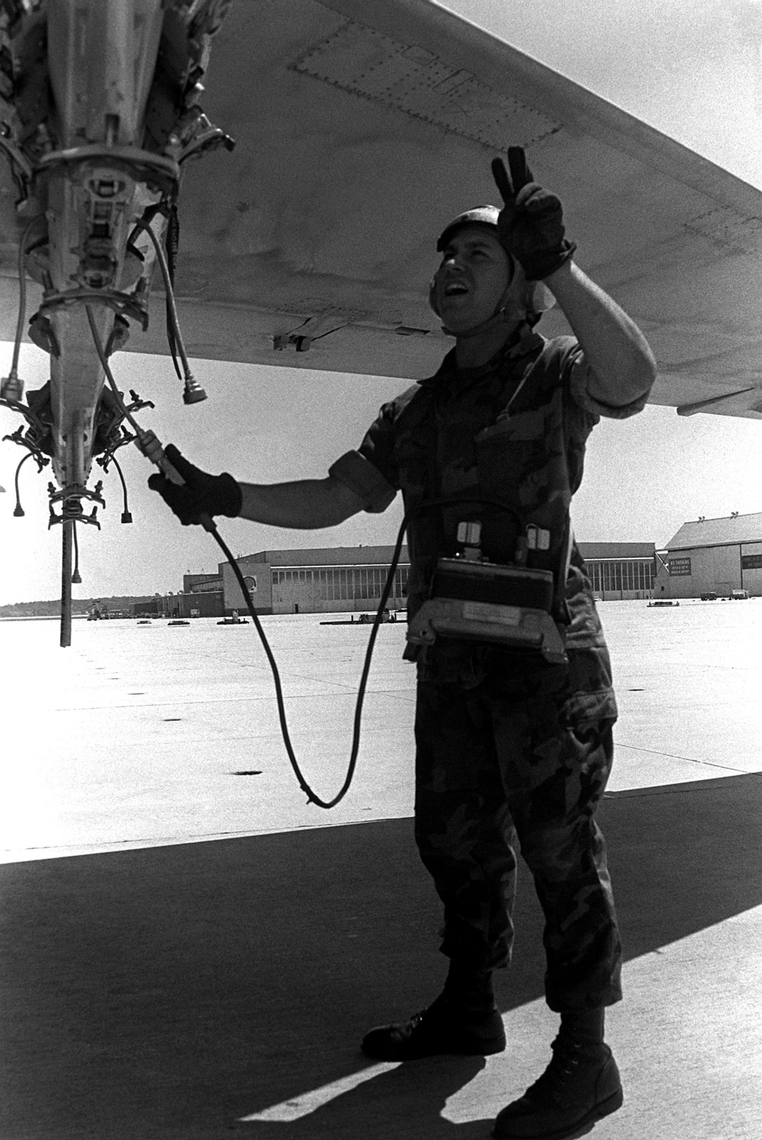 A member of Marine Attack Squadron 224 (VMA-224) signals to the cockpit while using an AN/AWM-54 aircraft firing circuit test set to test a multiple ejector rack (MER) on the wing of an A-6E Intruder aircraft
