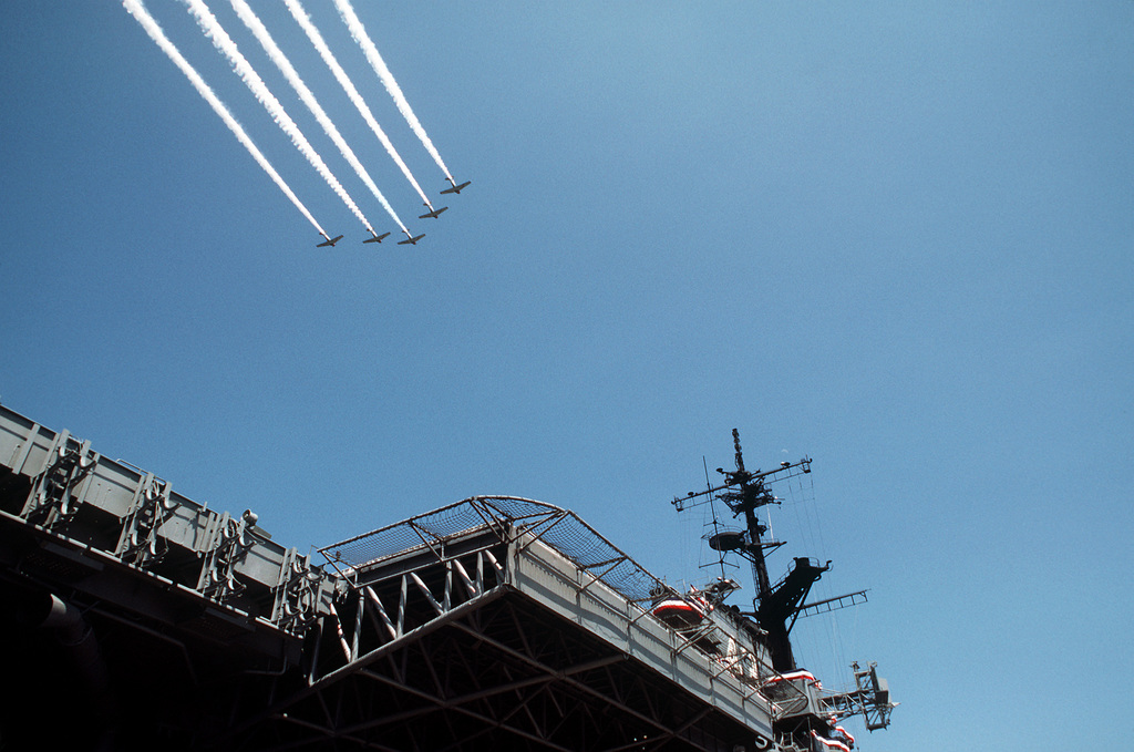 An aerobatic team passes over the aircraft carrier USS Coral Sea (CV-43) during the ship's decommissioning ceremony. The Coral Sea is being decommissioned after nearly 43 years of service