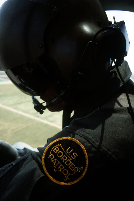 A member of the U.S. Border Patrol observes an area from the air during Operation Alliance, a project of Joint Task Force 6 (JTF-6). JTF-6 is the unit charged with monitoring borders between Texas, New Mexico, Arizona and Mexico. The U.S. Combat Pictorial Detachment is providing photographic coverage as part of the 5th Army's involvement in the operation