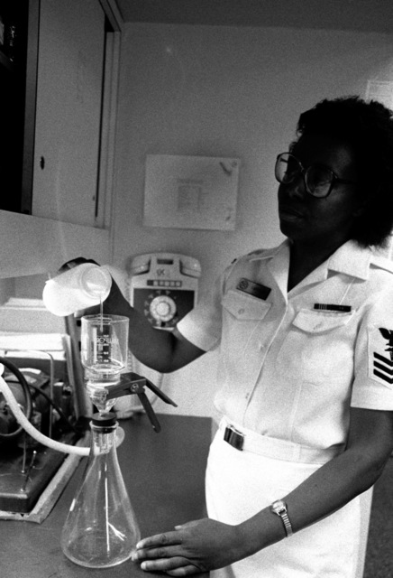 Hospital Corpsman 1ST Class Edna Garrison tests a sample of a tap water for bacteria in a Directorate of Occupational Health and Preventive Medicine (DOH/PM) laboratory. DOH/PM, which is based at the hospital, provides health services for the 75 commands in the Rhode Island/southeastern Massachusetts area