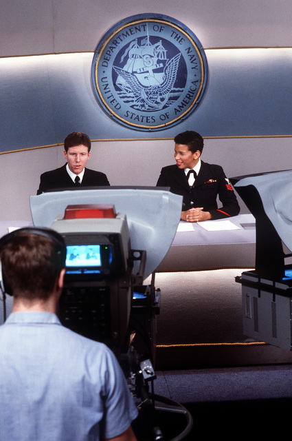 Journalist 1ST Class Johnnie Gaines listens as SENIOR CHIEF Journalist Paul Waldrop reports a story on the set of the Navy Broadcasting Service's Navy News This Week in the studio at the Naval Imaging Command