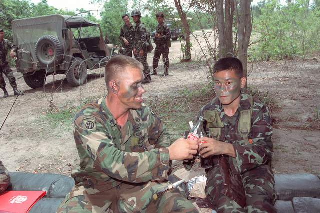 A staff sergeant from 4th Bn., 22nd Inf., 25th Inf. Div. (Light), toasts his Thai counterpart with a soft drink during a break in training conducted as part of the combined Thai/U.S. exercise Cobra Gold '90
