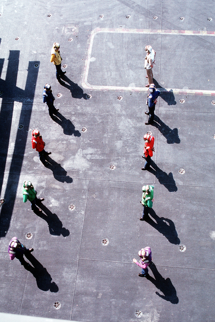 Flight deck crew members serving as sideboys wait for the arrival of Vice President Dan Quayle and Mrs. Quayle aboard the nuclear-powered aircraft carrier USS DWIGHT D. EISENHOWER (CVN-69)