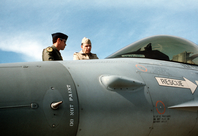 Admiral Jonathan T. Howe, right, Commander in CHIEF, Allied Forces Southern Europe, talks to a US Air Force officer as he views an F-16 Fighting Falcon aircraft being shown as part of a static display of NATO aircraft. The display is being held in conjunction with the NATO Southern Region exercise DRAGON HAMMER '90