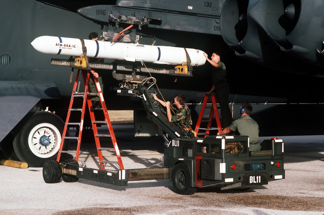 STAFF Sergeant Richard Pulaski, left, AIRMAN Christian Canada, AIRMAN Vincent Giasco and Sergeant William Reid mount an AIM-84A Harpoon missile on the wings pylon of a 60th Bombardment Squadron B-52G Stratofortress aircraft in preparation for a training exercise