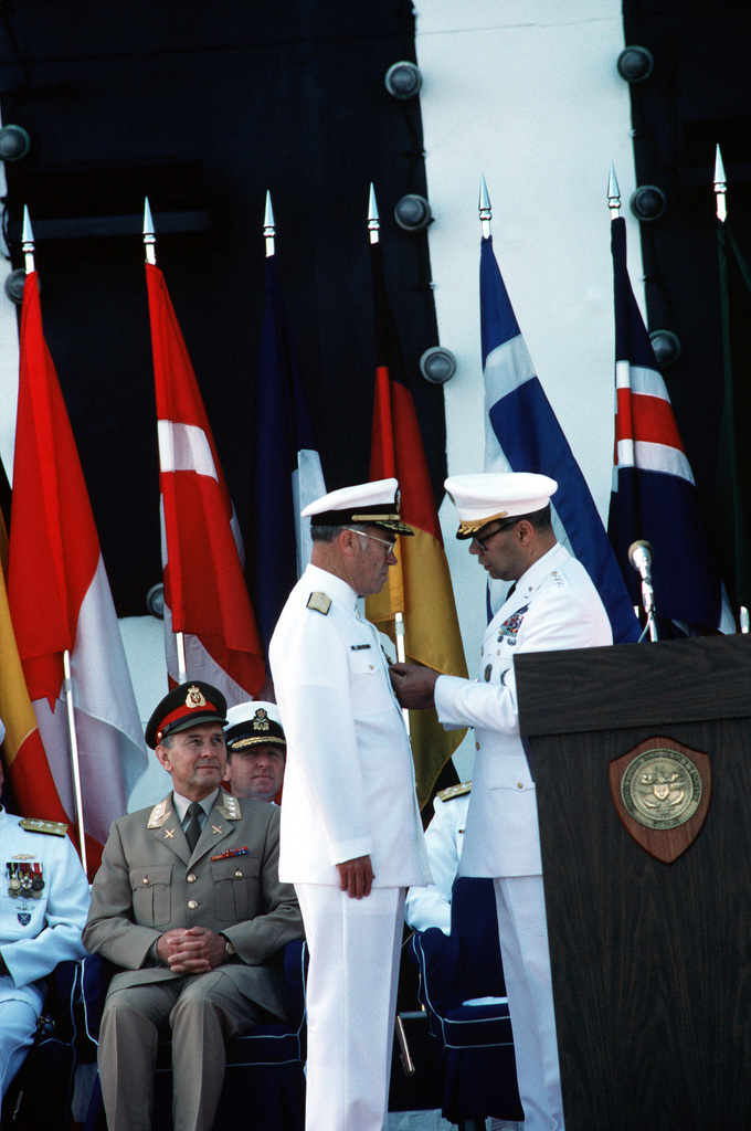 General Colin L. Powell, United States of America, Chairman, Joint Chiefs of STAFF, pins a medal on Admiral Frank B. Kelso II during the change of command ceremony at which Kelso relinquishes his position as Commander in CHIEF, United States Atlantic Command, to Admiral Leon A. Edney. The ceremony is taking place aboard the aircraft carrier USS JOHN F. KENNEDY (CV 67). Kelso will be replacing Admiral Carlisle A.H. Trost as CHIEF of Naval Operations
