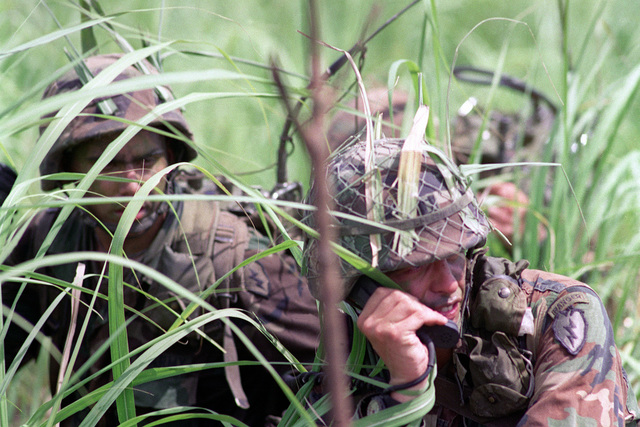 CAPT. Matt R. Litchfield, right, commanding officer, Co. A, 4th Bn., 22nd Inf., 25th Inf. Div. (Light), uses a field radio to communicate as his company nears its objective during the combined Thai/U.S. exercise Cobra Gold '90