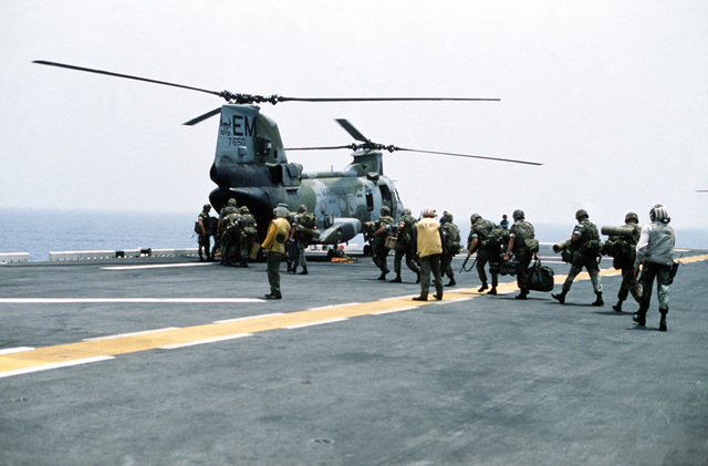 Marines of the 22nd Marine Expeditionary Unit (22nd MEU) file aboard a Marine Medium Helicopter Squadron 261 (HMM-261) CH-46E Sea Knight helicopter on the flight deck of the amphibious assault ship USS SAIPAN (LHA-2) during a rehearsal for Operation Sharp Edge. The SAIPAN is on station off the coast of Liberia