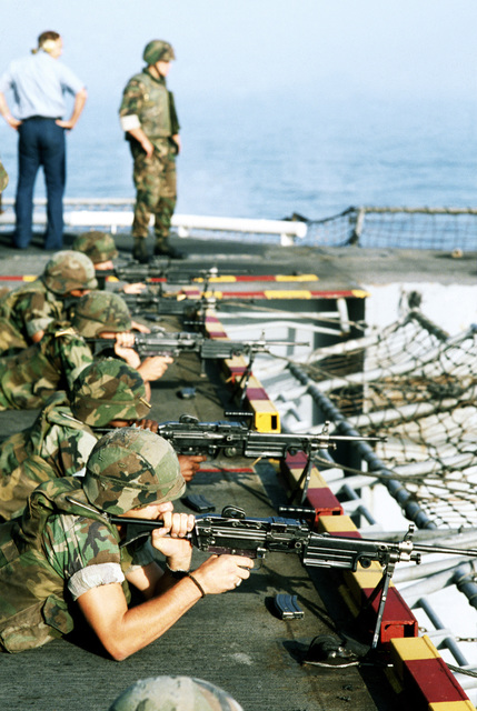 Marines of the 22nd Marine Expeditionary Unit prepare to fire their M-249 squad automatic weapons from the stern of the amphibious assault ship USS SAIPAN (LHA-2) during weapons training held prior Operation Sharp Edge. The SAIPAN is on station off the coast of Liberia