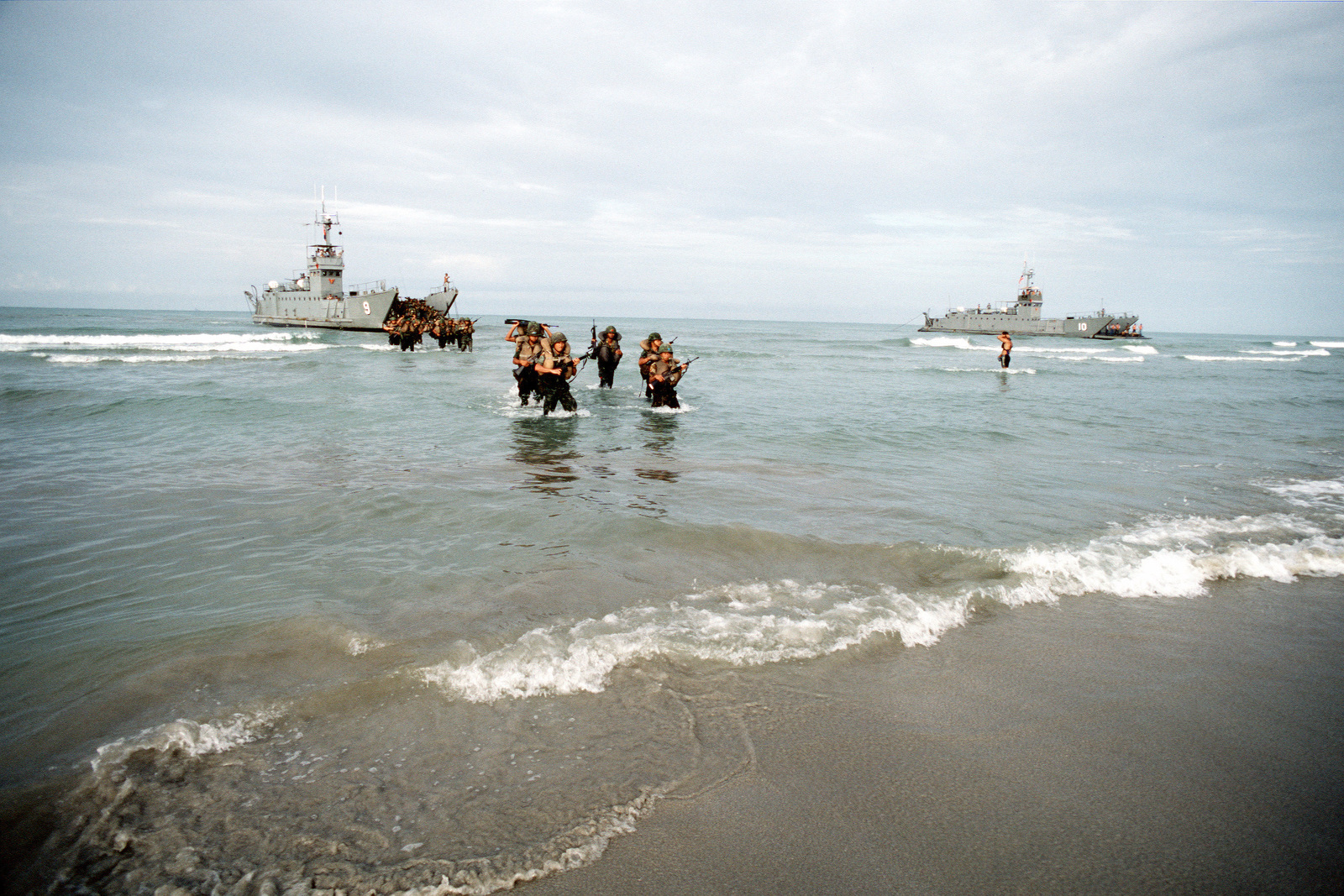 Thai marines wade ashore from the Royal Thai Navy utility landing craft WANG NOK (LCU-9) during the combined Thai/U.S. exercise Cobra Gold '90. The Thai utility landing craft WANG NAI (LCU-10) is at right