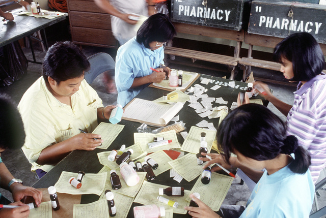 Volunteers working with the 3rd Tactical Fighter Wing's medical civic action program (MEDCAP) team fill prescriptions at the Santa Rosa School. The school is being used as a clinic for more than 1,300 evacuees who have fled the mudslides and flooding caused by heavy rains that fell following the eruption of Mount Pinatubo