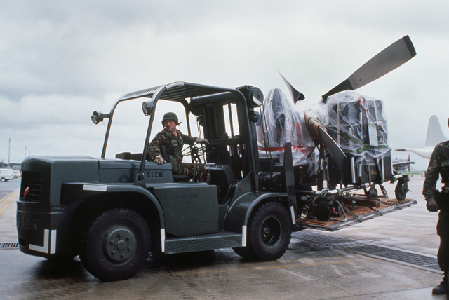 A member of the 603rd Aerial Port squadron uses a forklift to transport supplies and a propeller across the airfield. The 374th Tactical Airlift Wing material has been delivered to the base for the wing's use during Exercise Purple Duck 90-22