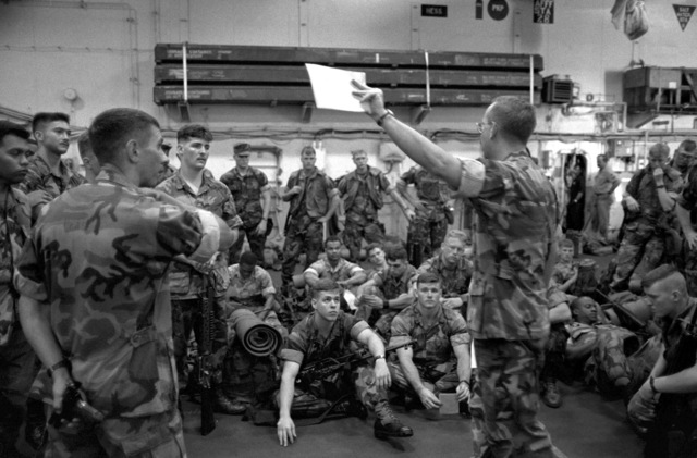 Marines of the 22nd Marine Expeditionary Unit (22nd MEU) gather in the hangar bay aboard the amphibious assault ship USS SAIPAN (LHA 2) for a briefing on the situation in and around Monrovia, Liberia, and the rules of engagement governing their mission once ashore. The SAIPAN is on station off the coast of Liberia for Operation Sharp Edge
