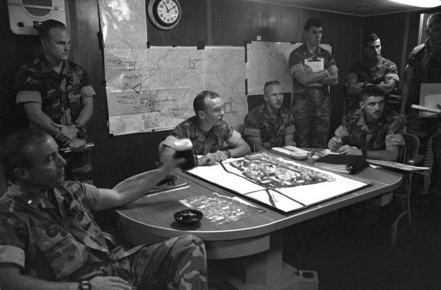 Officers of the 22nd Marine Expeditionary Unit (22nd MEU) gather in the MEU commander's office aboard the amphibious assault ship USS SAIPAN (LHA 2) for a briefing on the situation in and around Monrovia, Liberia. The SAIPAN is on station off the coast of Liberia for Operation Sharp Edge