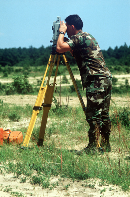 A US Air Force civil engineering non-commissioned officer uses a laser measuring system to determine the distance from the impact point to where simulated heavy equipment has landed during AIRLIFT RODEO '90. AIRLIFT RODEO is an annual airdrop competition that tests the flight and ground skills of Military Airlift Command aircrews as well as foreign teams.